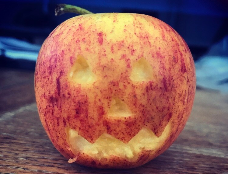 A red apple with a spooky halloween pumpkin face carved into it.